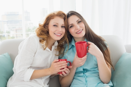 Portrait of two happy young female friends with coffee cups in the living room at home photo