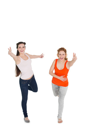 Full length of two cheerful young female friends with hand gestures over white background photo