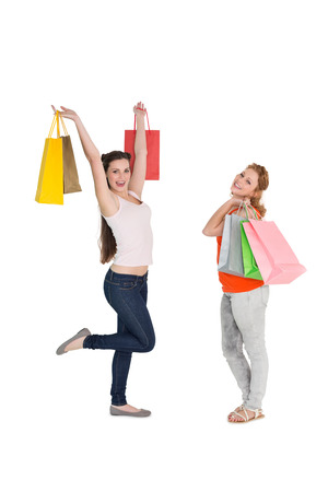 Full length of two happy young female friends with shopping bags over white background photo