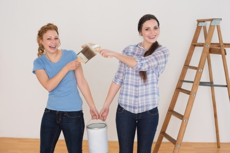 Two cheerful female friends  holding paint brushes and can in a new house photo