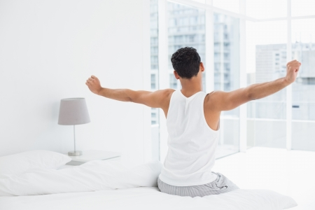 waking up: Rear view of a young man waking up in bed and stretching his arms Stock Photo