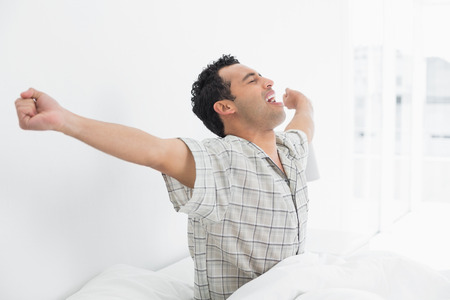 Side view of a happy young man waking up in bed and stretching his arms photo