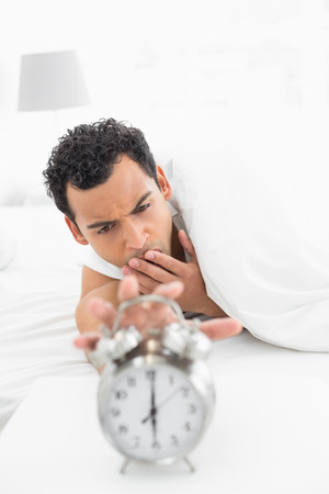 Close-up of a sleepy young man in bed extending hand to alarm clock at home photo