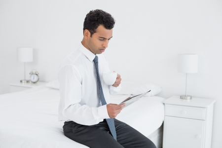 Side view of a young businessman with coffee cup reading newspaper at a hotel room photo