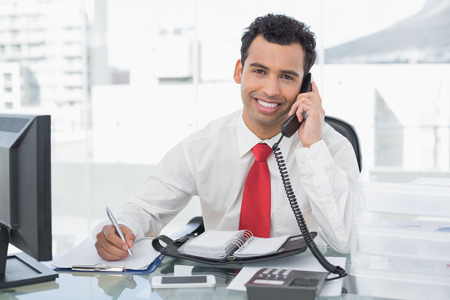 Portrait of a smiling businessman writing notes while using land line phone at a bright office photo