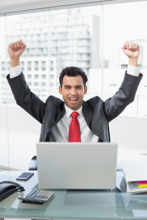 Portrait of a businessman cheering with clenched fists in front of laptop at office desk photo