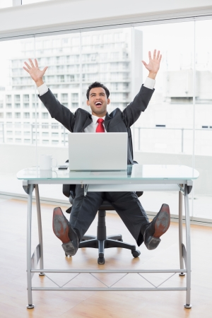 opgeheven handen: Elegant businessman cheering with raised hands in front of laptop at office desk