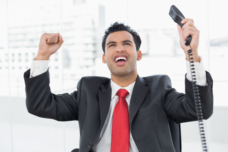 Elegant businessman cheering with telephone receiver at a bright office photo
