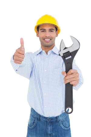 Portrait of a smiling young handyman holding out a wrench while gesturing thumbs up against white background photo
