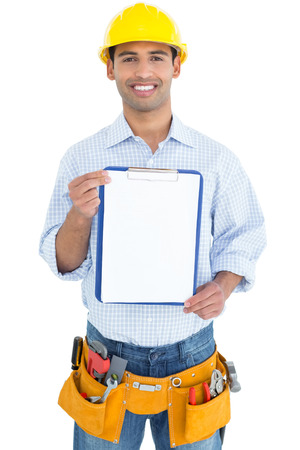 Portrait of a smiling handyman in yellow hard hat holding a clipboard against white background photo