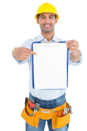 Portrait of a smiling handyman in yellow hard hat pointing at clipboard against white background photo