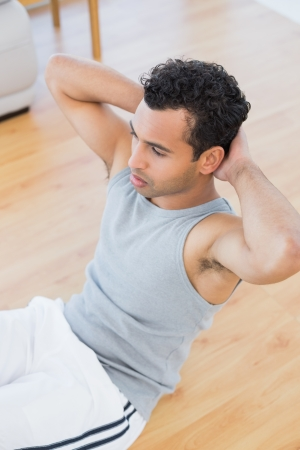 crunches: High angle view of a young man doing abdominal crunches in the living room at house
