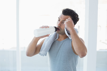 Tired young man drinking water while wiping sweat with towel in a bright fitness studio photo