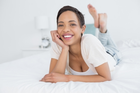 Portrait of a smiling pretty young woman relaxing in bed photo