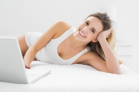 Portrait of a smiling young woman using laptop in bed at home Stock Photo - 25465062