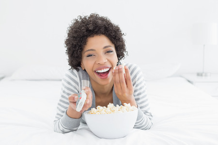 Portrait of a cheerful young woman with remote control and popcorn bowl lying in bed at home photo