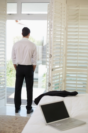 facing away: Full length of a businessman looking through window at a hotel bedroom