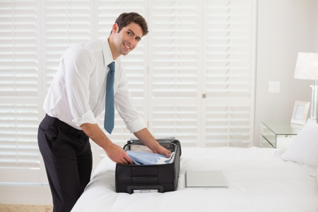 Side view portrait of a smiling businessman unpacking luggage at a hotel bedroom Stock Photo
