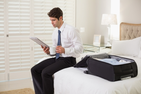 Young businessman with coffee cup reading newspaper by luggage at a hotel room photo