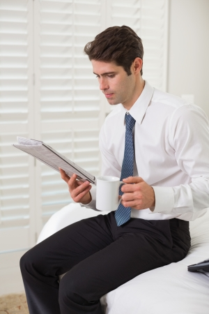Serious young businessman with coffee cup reading newspaper at a hotel room photo