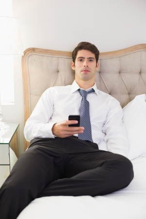 Portrait of a serious well dressed man with cellphone sitting in bed at home photo