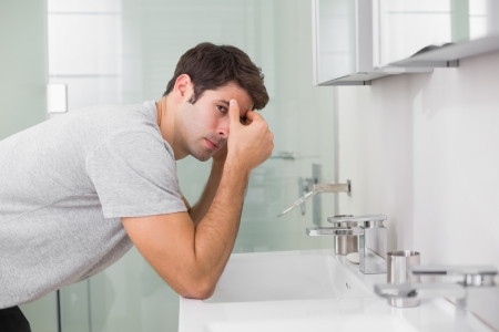 tensed: Side view of a tensed young man at washbasin in bathroom Stock Photo