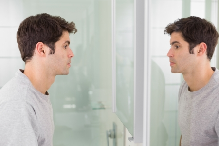 reflection in mirror: Side view of a tensed young man looking at self in mirror in the bathroom