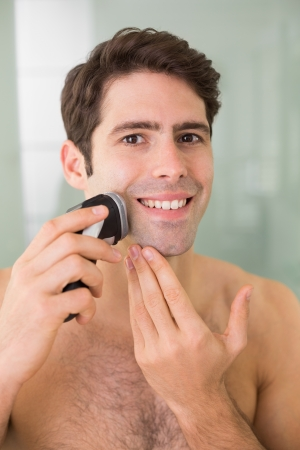electric razor: Portrait of a smiling handsome young shirtless man shaving with electric razor