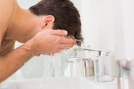 Zijaanzicht van een shirtless jonge man gezicht wassen in de badkamer