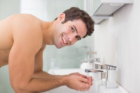 Seitenansicht Porträt eines shirtless jungen Mann Waschen Gesicht im Bad