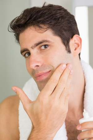 Close up portrait of a handsome young man applying moisturizer on his face Stock Photo