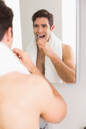 Young shirtless man with reflection brushing teeth in the bathroom photo