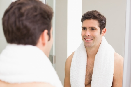 Rear view of a young man smiling at self in mirror in the bathroom
