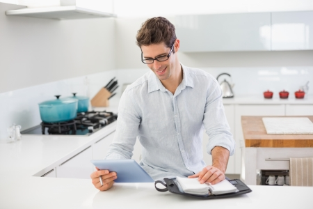 Happy casual young man with digital tablet and diary in kitchen at home photo
