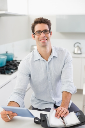 Portrait of a cheerful casual young man with digital tablet and diary in kitchen at home photo
