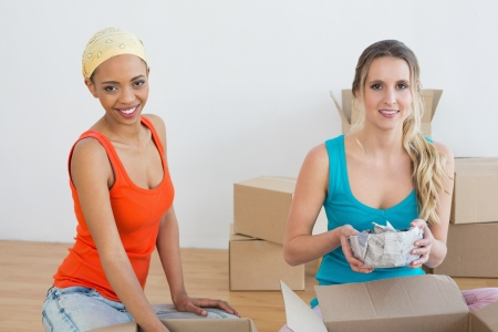 Portrait of two friends moving together in a new house and unwrapping boxes photo