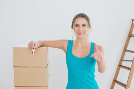 Portrait of a happy young woman with keys, boxes gesturing thumbs up in a new house Stock Photo - 25466404
