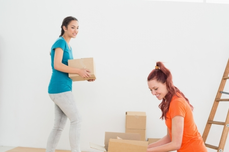 Two friends moving together in a new house and unwrapping boxes photo