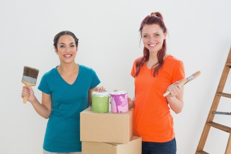 Portrait of two happy female friends holding paint brushes with cans and boxes in a new house photo