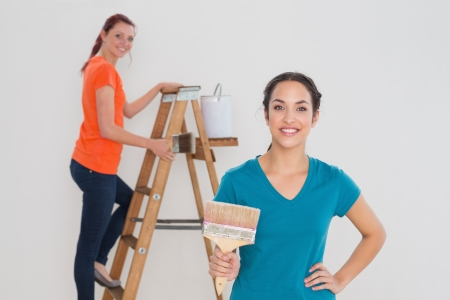 Two happy female friends with paint brushes and ladder against white background photo