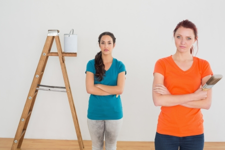 Portrait of two female friends with paint brushes and ladder in a new house photo