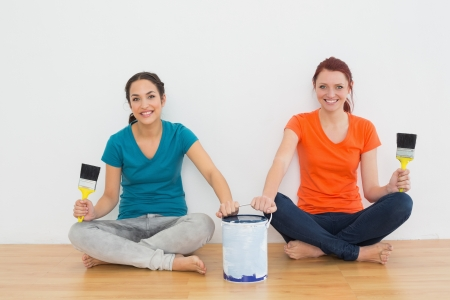 Portrait of two smiling female friends with brushes and paint can sitting in a new house photo