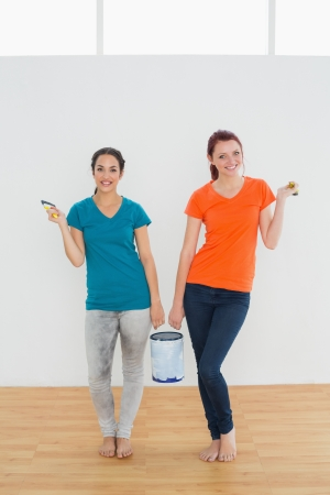 Full length portrait of two smiling female friends with brushes and paint can standing in a new house photo