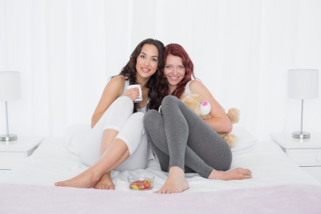 Portrait of happy young female friends with coffee cups in bed at home photo