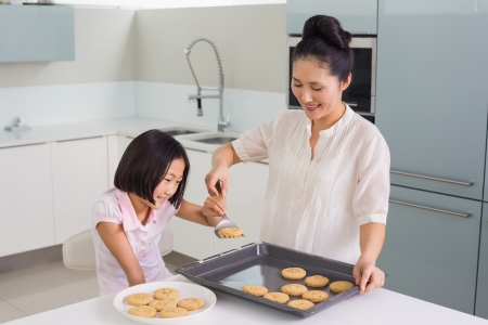 Young girl helping her mother prepare cookies in the kitchen at home
