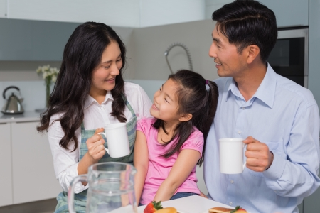 Happy young girl enjoying breakfast with parents at table in the house photo