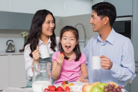 people eating: Portrait of a happy young girl enjoying breakfast with parents in the house Stock Photo