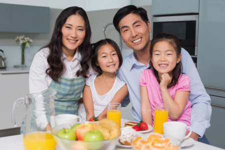Portrait of a cheerful family of four enjoying healthy breakfast in the kitchen at home Reklamní fotografie