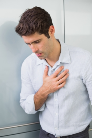 Casual young man with chest pain standing at home photo