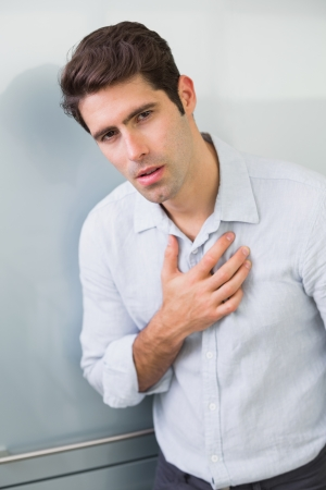 Portrait of a casual young man with chest pain standing at home photo